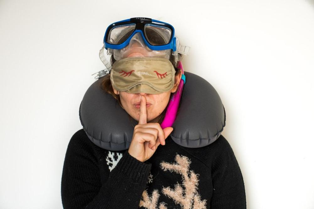 Sandra with a snorkel, a sleeping mask and a travel pillow