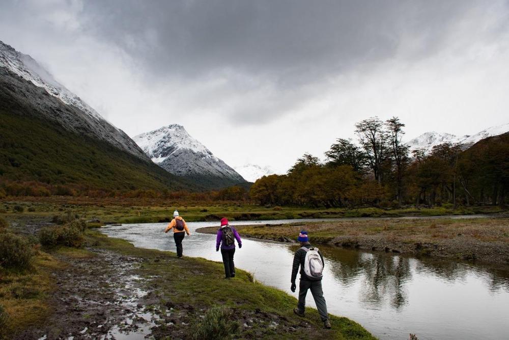 3 people walking by the river, dark clouds in the sky