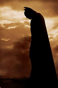 Batman stands moodily in a cloudy dark brown sky.