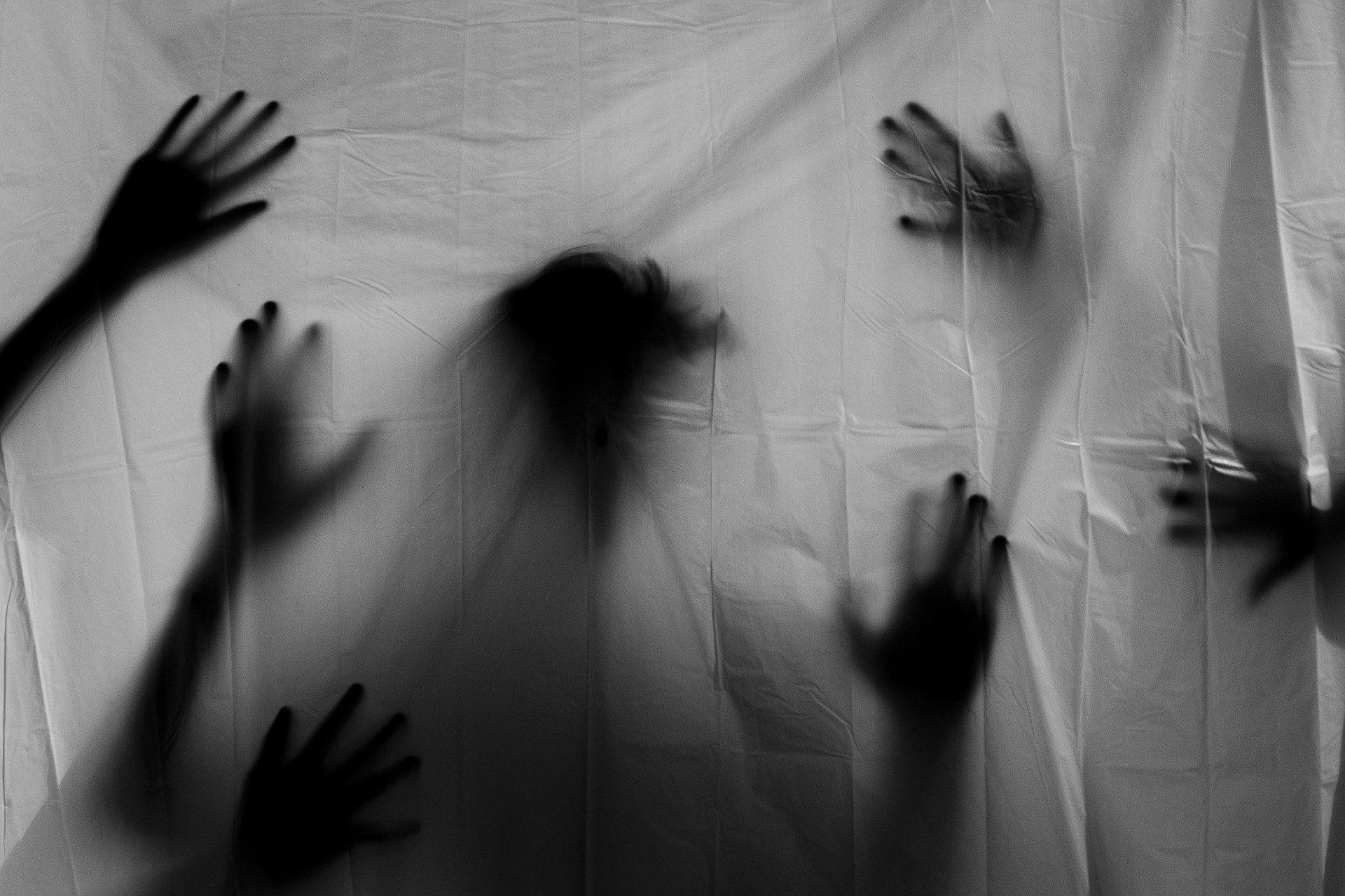 تمثل الصورة ظلا لجسم وأيدي كثيرة من وراء ستار كتوضيح لحالة الكاتب