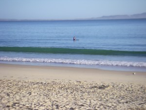 Noosa Main Beach lone paddler stretching out.