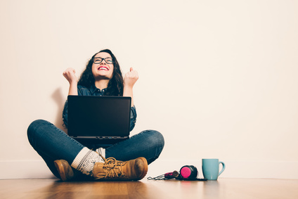 Woman sitting on the floor with a laptop raising his arms with a look of success