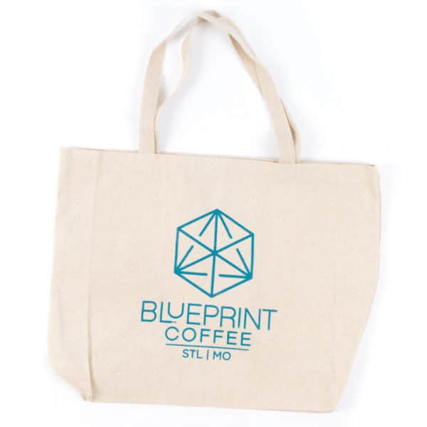 "A canvas tote bag bearing the Blueprint Coffee vertical logo in ""Blueprint"" blue screen print."
