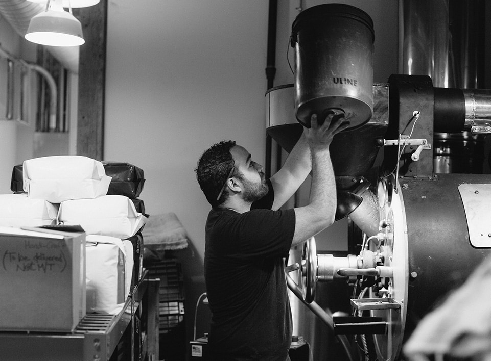 Mazi Razani loads green, unroasted, coffee into the Gothot roaster at Blueprint Coffee.