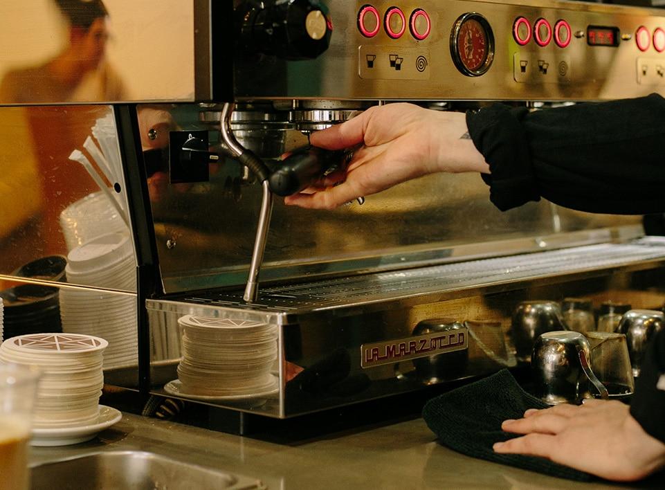 roy brady of la marzocco inserts a handle of espresso into the linea