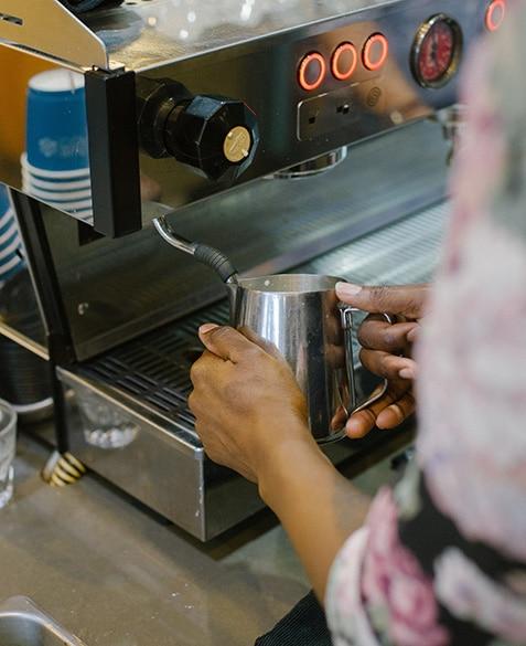Janelle Johnson steams milk on the La Marzocco Linea PB at Blueprint Coffee Delmar.