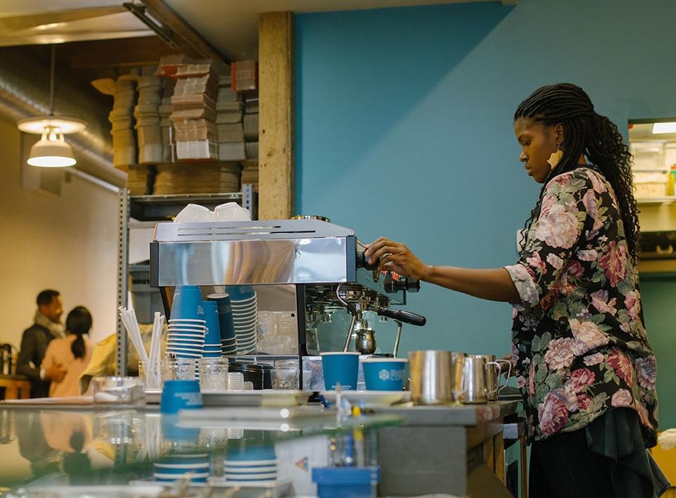Janelle prepares drinks on the espresso bar at Blueprint Coffee Delmar.