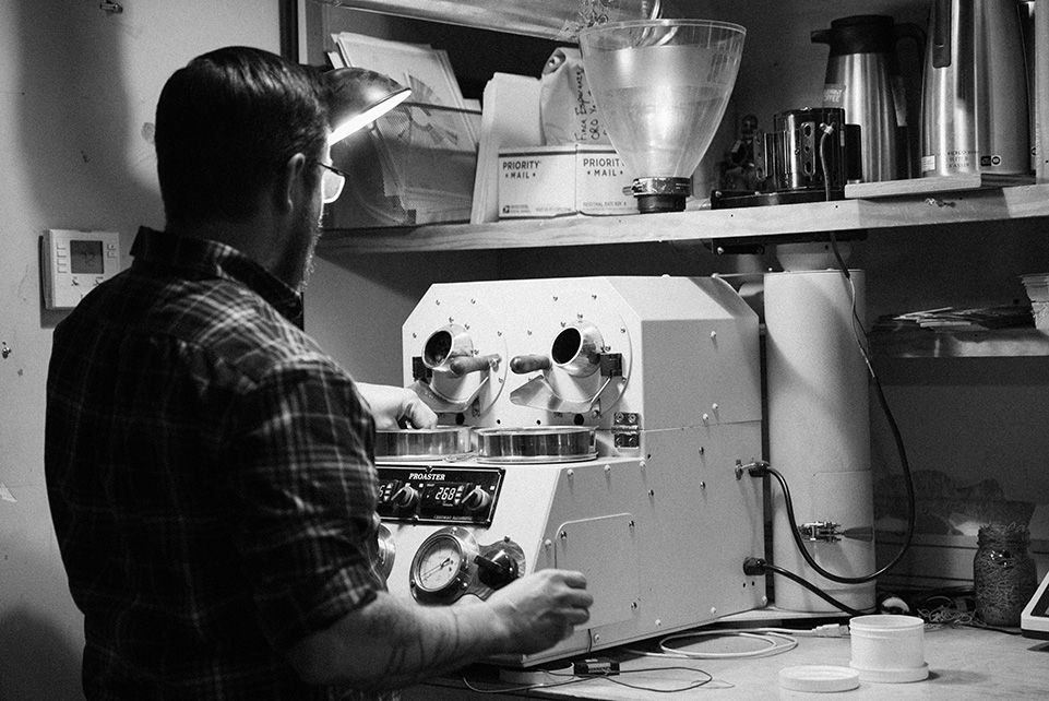 Andrew Timko at the sample roaster in the production area of Blueprint Coffee on Delmar Blvd.