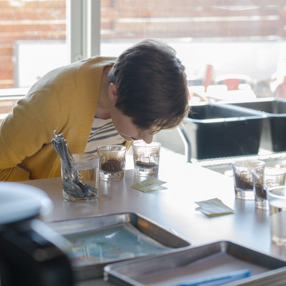 A taster smells freshly ground coffee to evaluate its fragrance during a cupping.