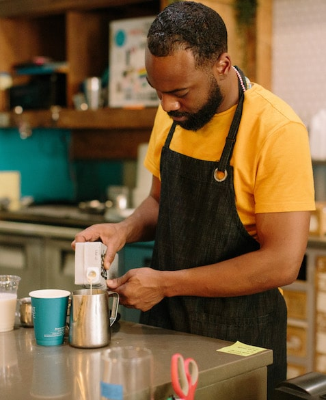 El Strickland pours milk into a coffee