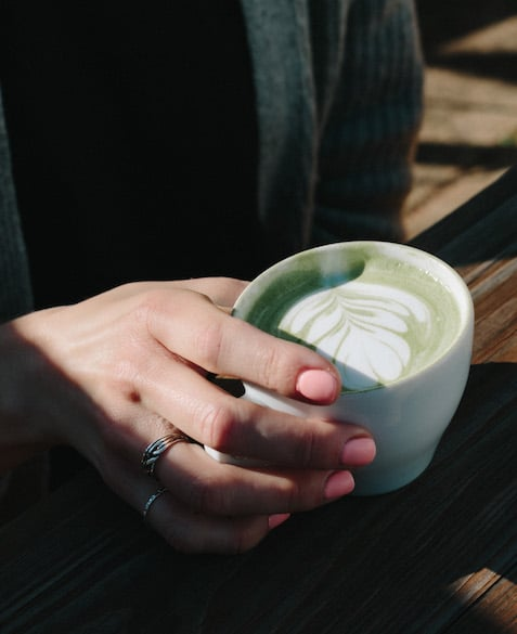 A hand holding a matcha tea latte with steamed milk flower art in a coffee mug