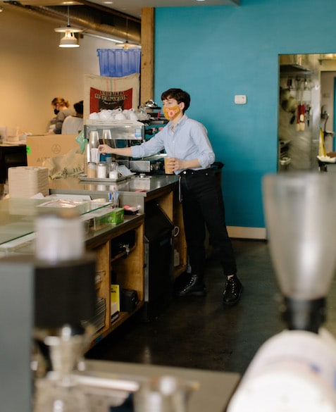 Mac makes an iced coffee near the espresso machine