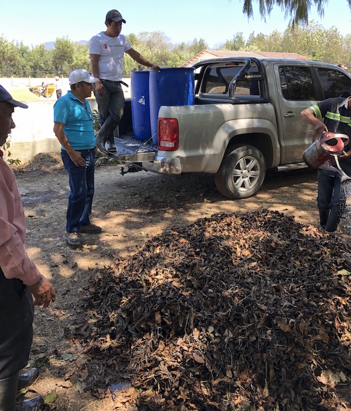 Coffee farmers look at their composting pile while standing next to a truck.