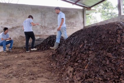Coffee farmers stand next to their composting pile.