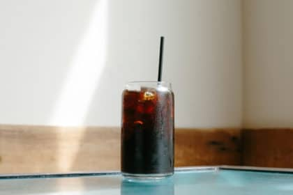 A glass of cold brew coffee sitting on a teal table at home.