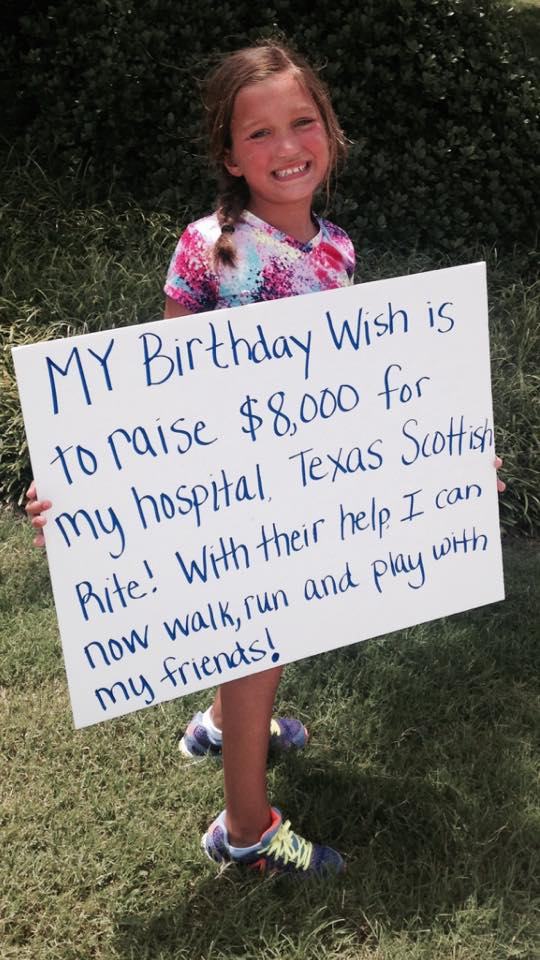 Addison Bryan Holding Up A Sign Saying My Birthday Wish Is To Raise 8,000 for my hospital, Texas Scottish Rite. With Their Help I Can Now Walk, Run And Play With My Friends