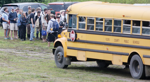 FloydFest patrons board school bus after parking at county commerce center lot.