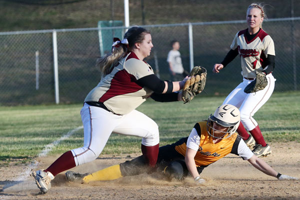 Sliding under the tag at third base.