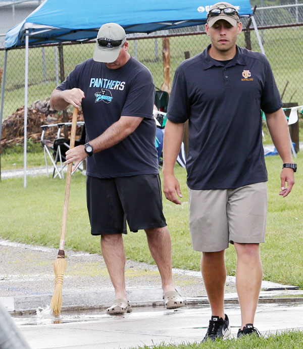 Clean-up at the shot put area of state meet on Friday.
