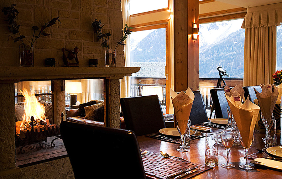 Chalet Serena Dining Table Fireplace lit mountains yoga retreat chamonix mont blanc france hiking retreats spa healthy food alps vegan vegetarian hot tub relax fitness