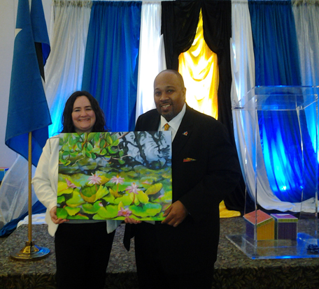 "Presenting ""In good company"" to Pres. of SLTA, Ross Cadastre-Cadasse, on behalf of Lisa Banks"