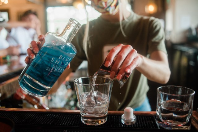 A bartender pours a shot of blue shark vodka