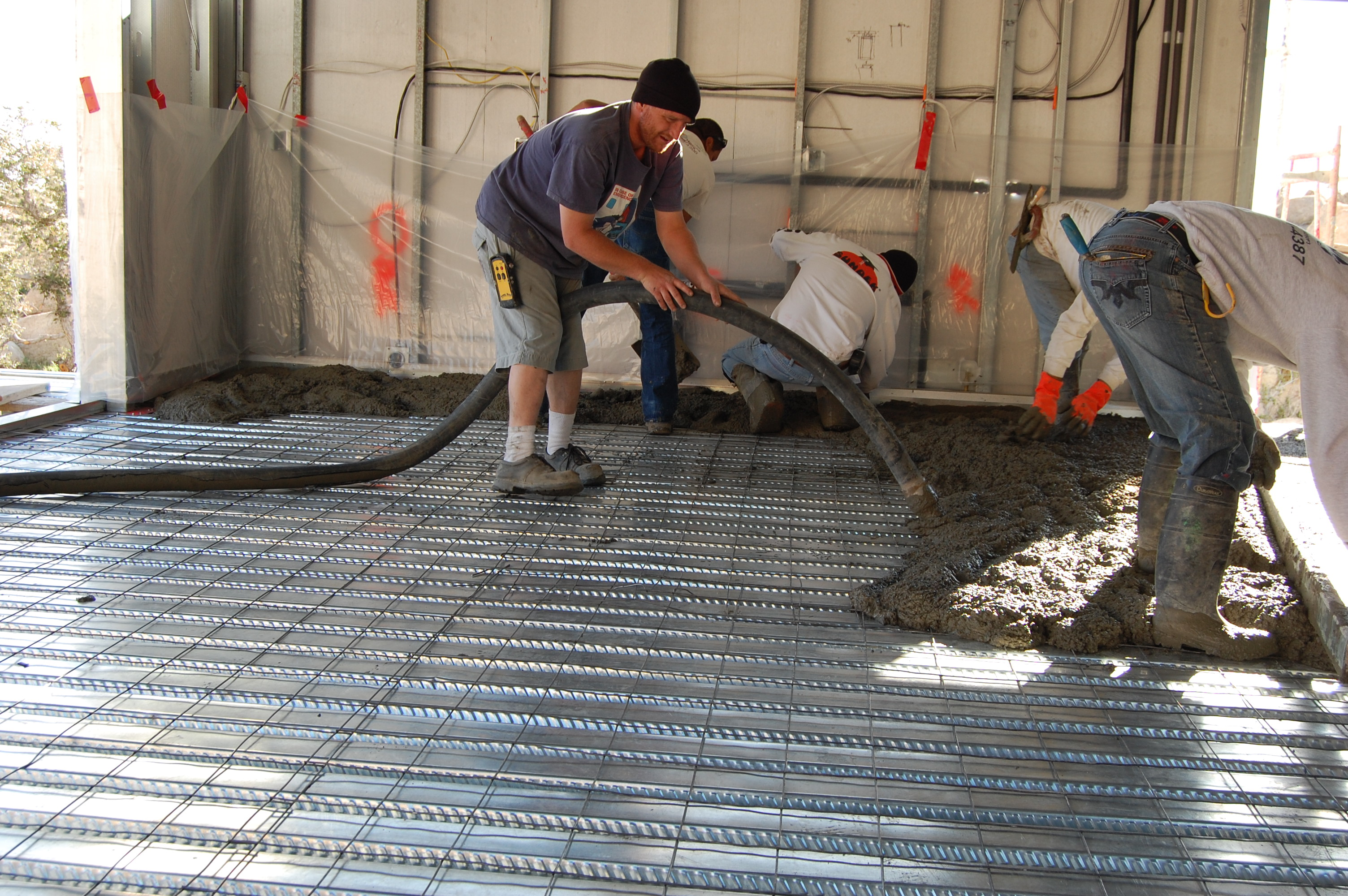 Wire mesh sits atop steel B decking as concrete is pumped.