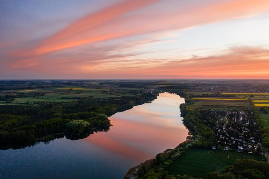 river surrounded by agricultural land at dusk with pink clouds reflecting in water; highlighting the dangers of pesticide runoff into water