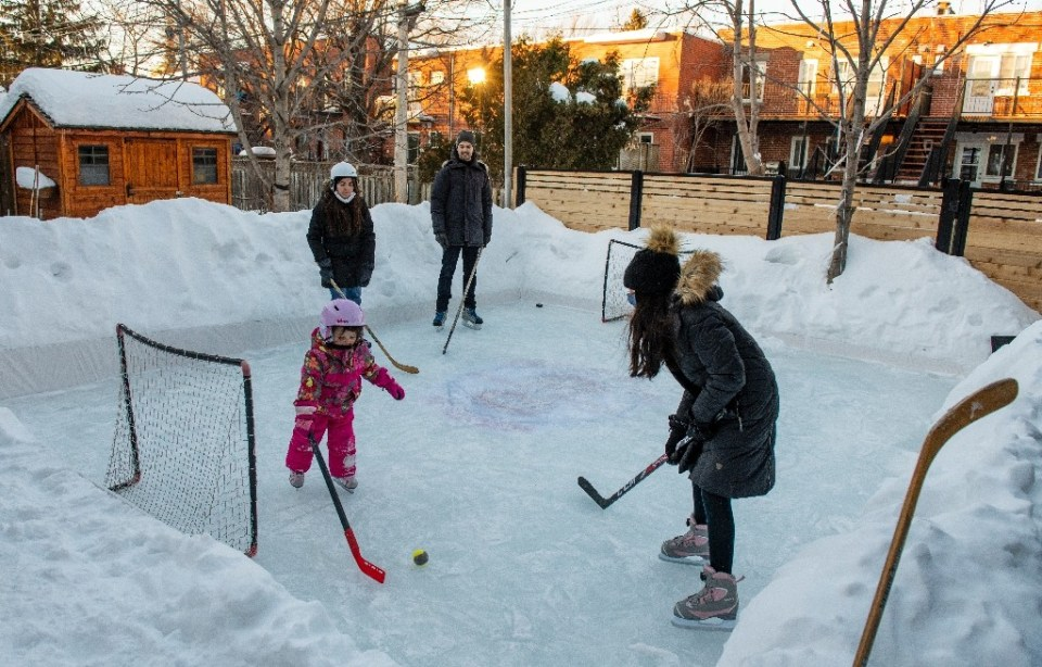Felix Rheaume (C) and his family play hockey on the ice rink in their backyard in Montreal - Sebastien St-Jean / ©AFP