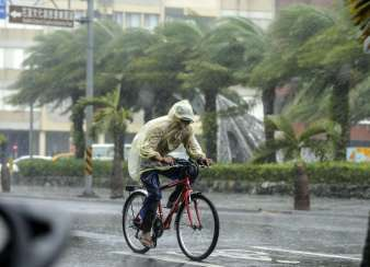 epa05557799 A man braves to heavy rains as typhoon Megi hits Hualien county, eastern Taiwan, 27 September 2016. Typhoon Megi hit Taiwan with heavy winds, causing coastal high waves and flooding rains, according to media reports. EPA/RITCHIE B. TONGO