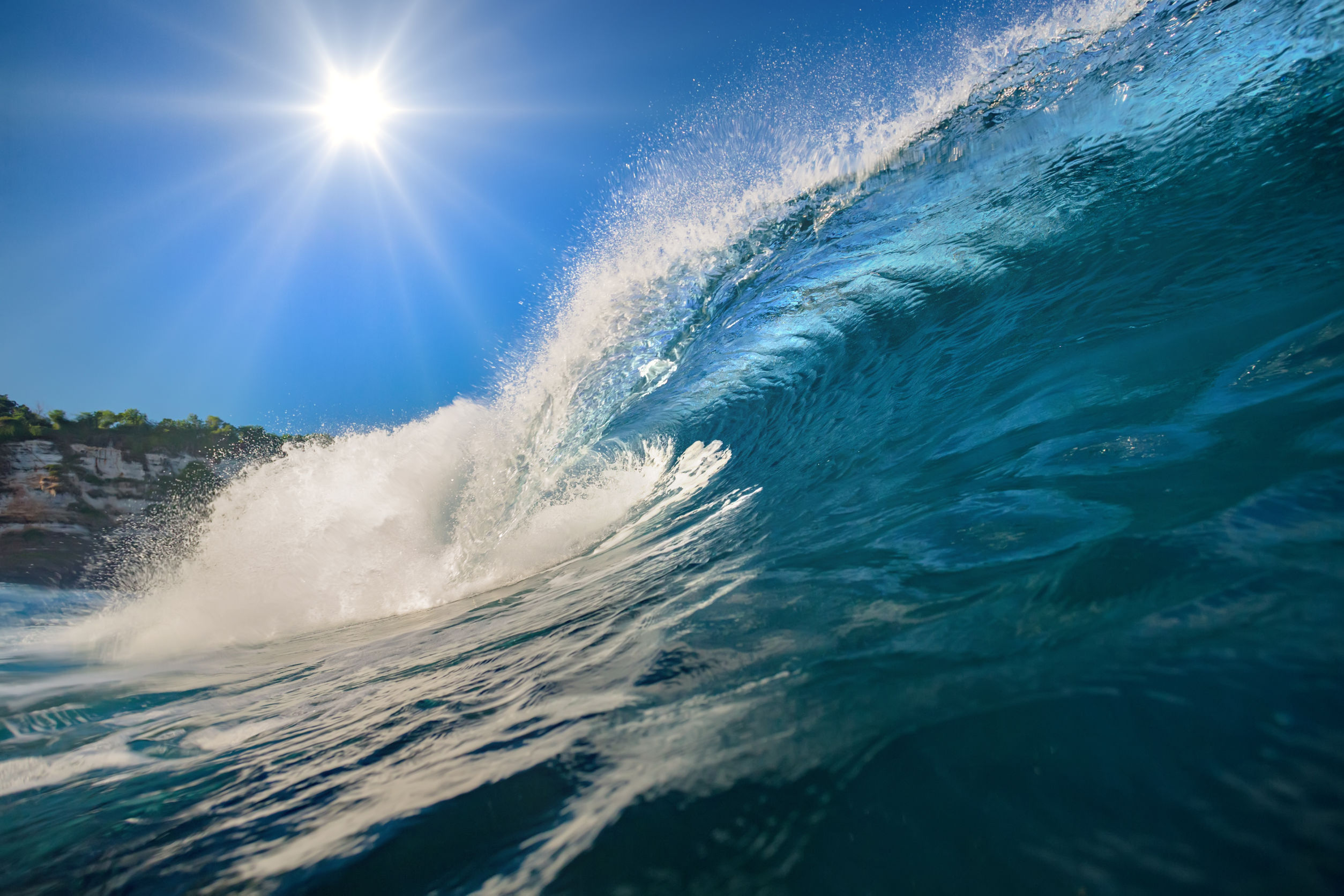 Blue Wave Rising with Sun and Blue Skys Above and a Bit of Shore and hillside in background