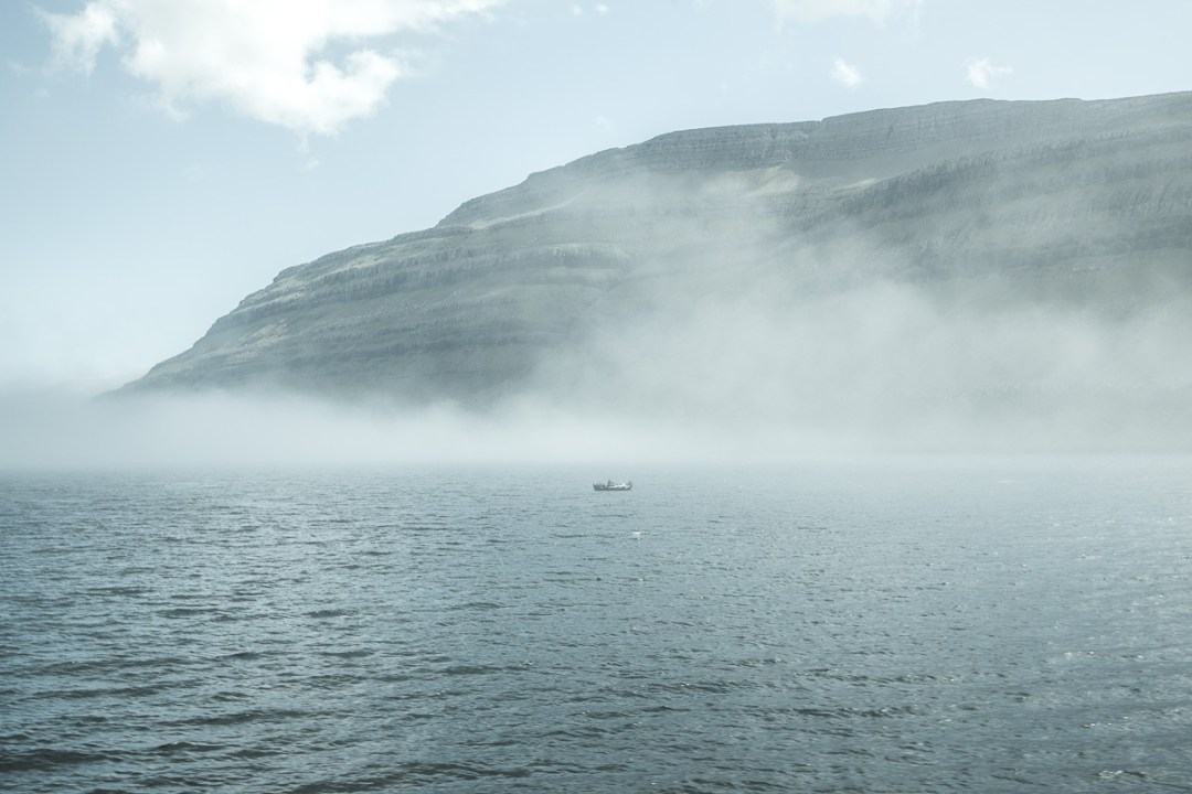 A lone boat in the fog, Faroe Islands. by Jon Armstrong for Blurbomat.com.