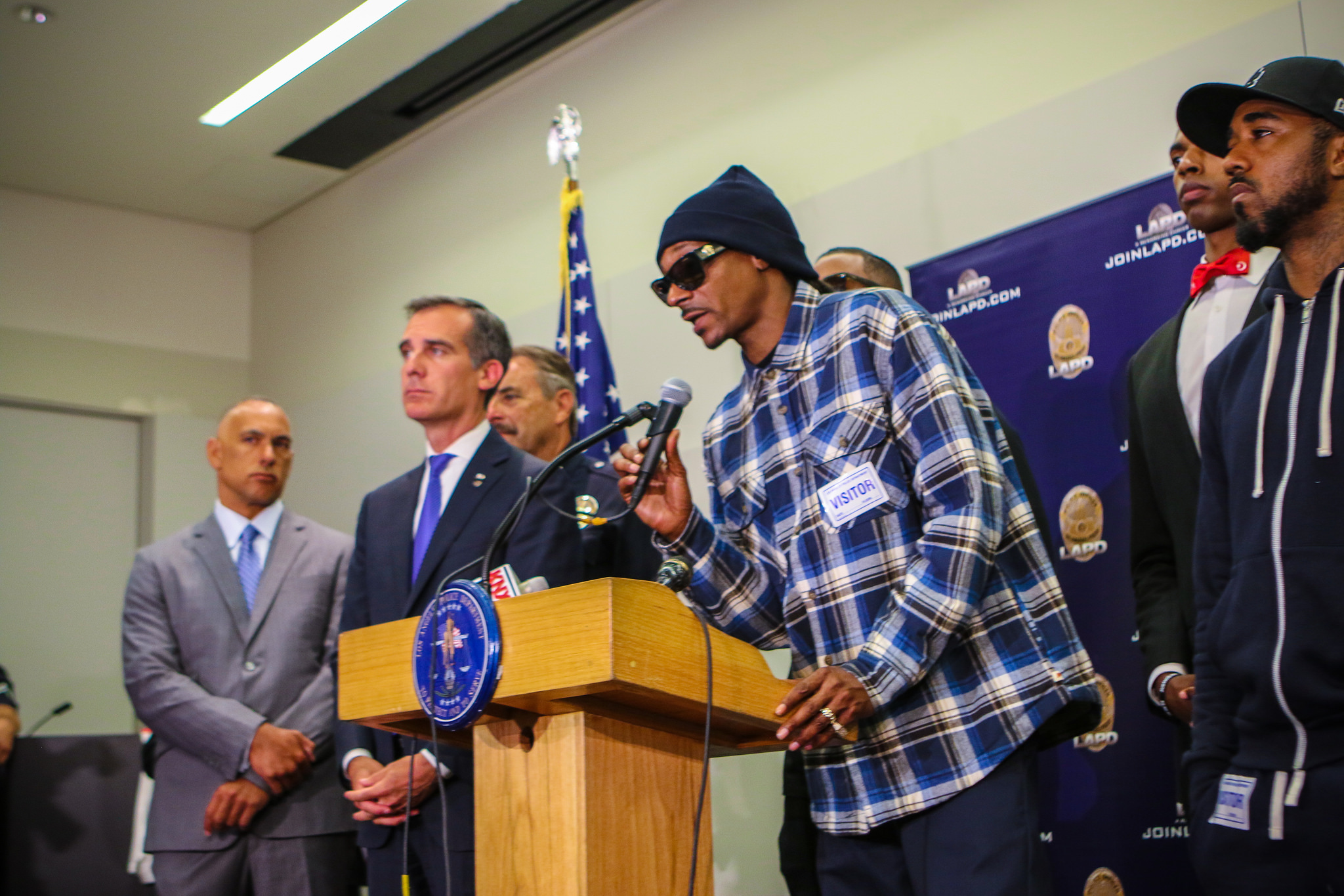 Snoop Dogg speaking at a press conference with LAPD Chief Beck, Mayor Garcetti, The Game, and community members after the police ambush in Dallas. (C) Eric Garcetti. License under CC BY 2.0.