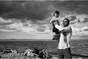 Lesbos, Greece, 2015: A father celebrates his family's safe passage to Lesbos after a stormy crossing over the Aegean Sea from Turkey. ©Tom Stoddart