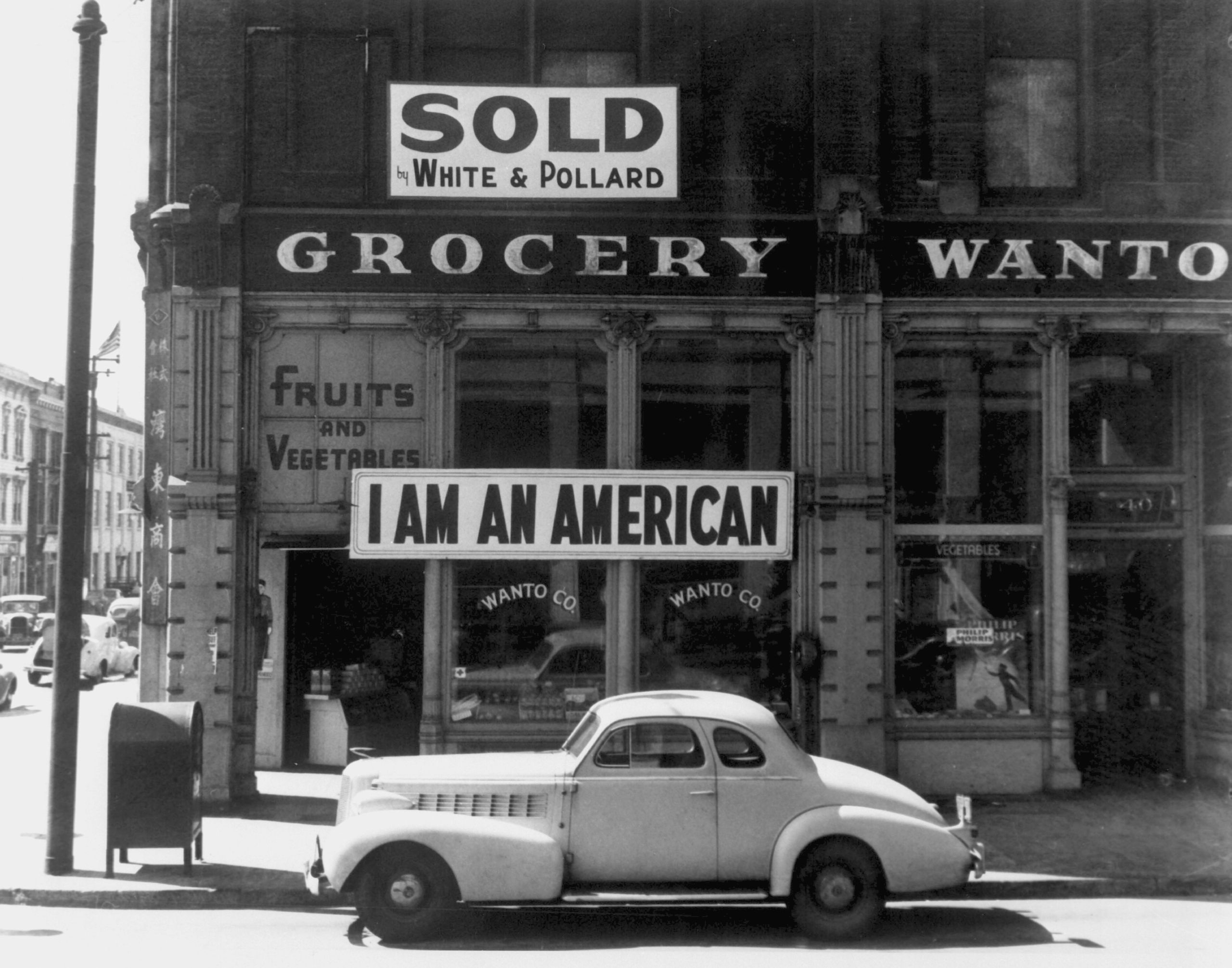A Japanese American unfurled this banner the day after the Pearl Harbor attack. This Dorothea Lange photograph was taken in March 1942, just prior to the man's internment. Photo by Dorothea Lange. [Public Domain]