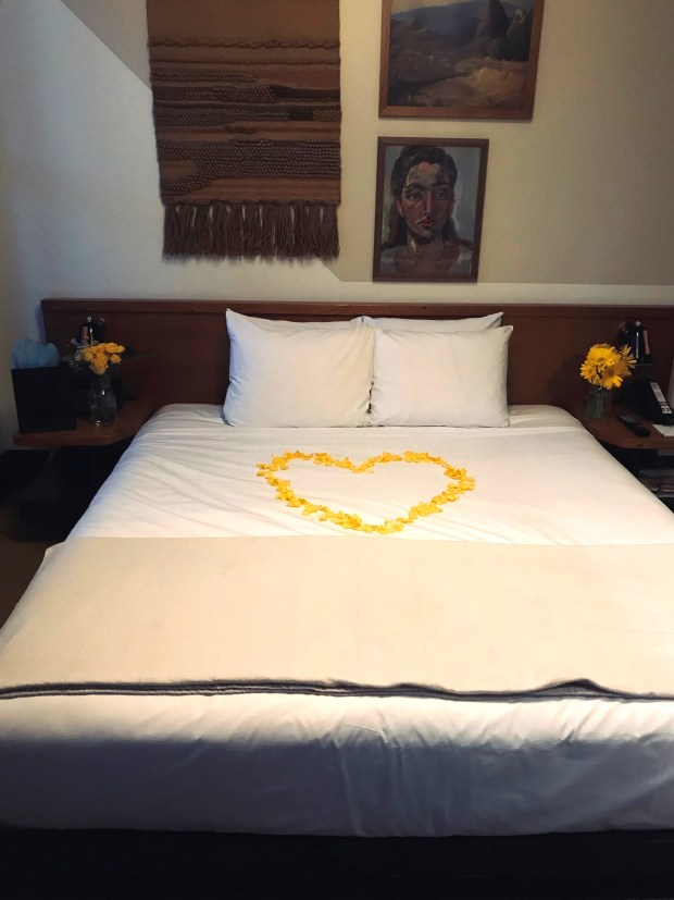 Flowers arrangements on both sides of the bed with a heart made of yellow rose petals in the center at The Freehand Hotel DTLA