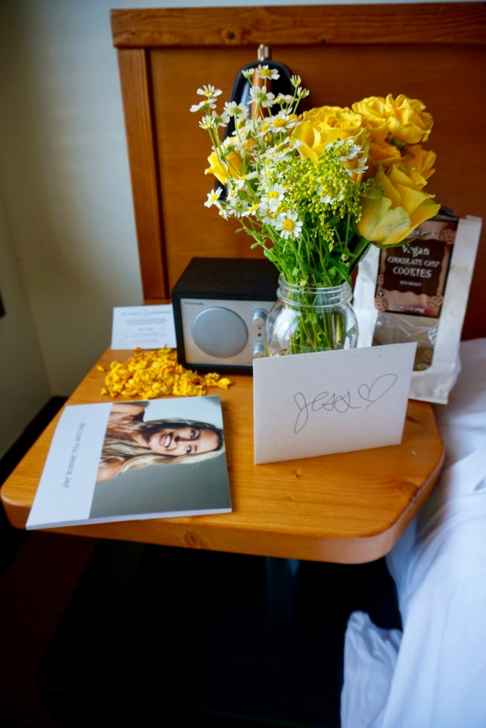 Jessica Jays bachelorette party decorations yellow flowers and photo book in the hotel room