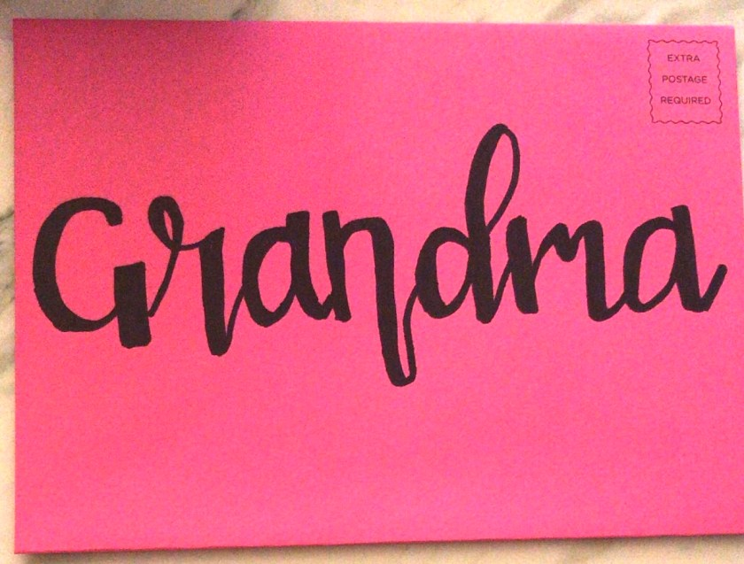 Hand lettering with a Sharpie Marker writing Grandma on a card envelope