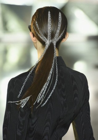 Model from Christian Siriano's runway with her hair in a low ponytail with silver chains woven through.