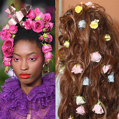 From designer Rodarte. One model has her hair up with faux flowers framing her face. The other model has her hair down in waves with flowers throughout