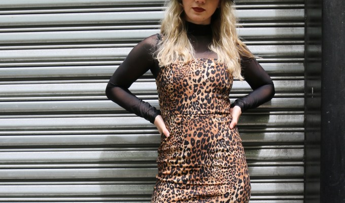 Image of FIT student Emma Strehle showcasing her personal street style in a cheetah print mini dress and black bucket hat.
