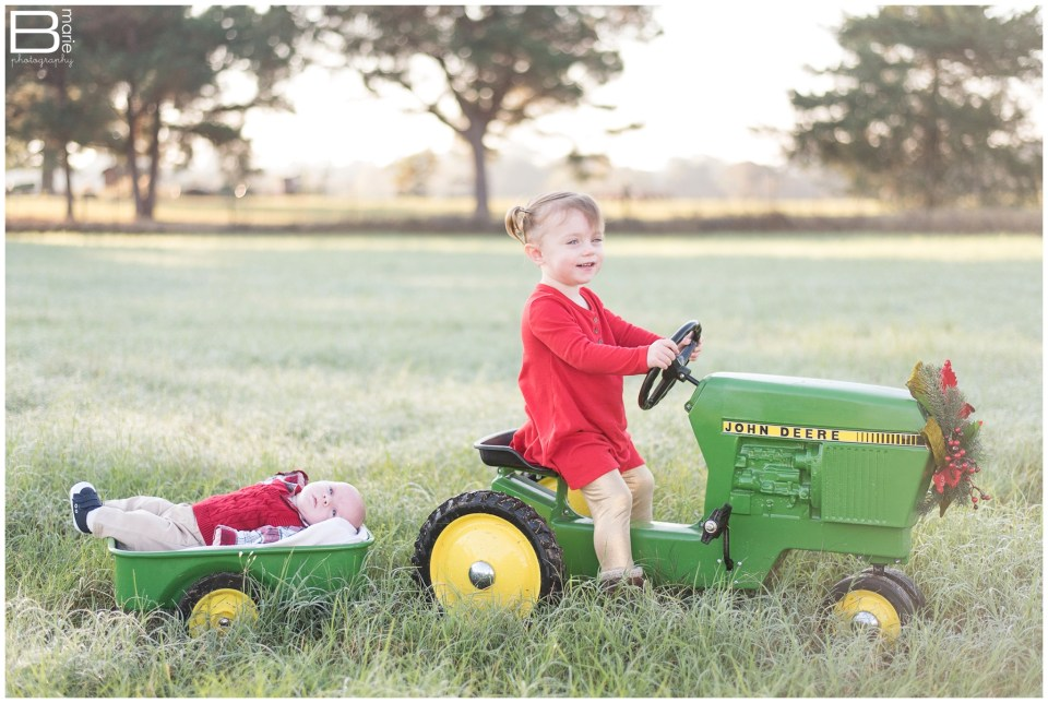 Kingwood family photographer fall family portrait session in open field with mini John Deere tractor