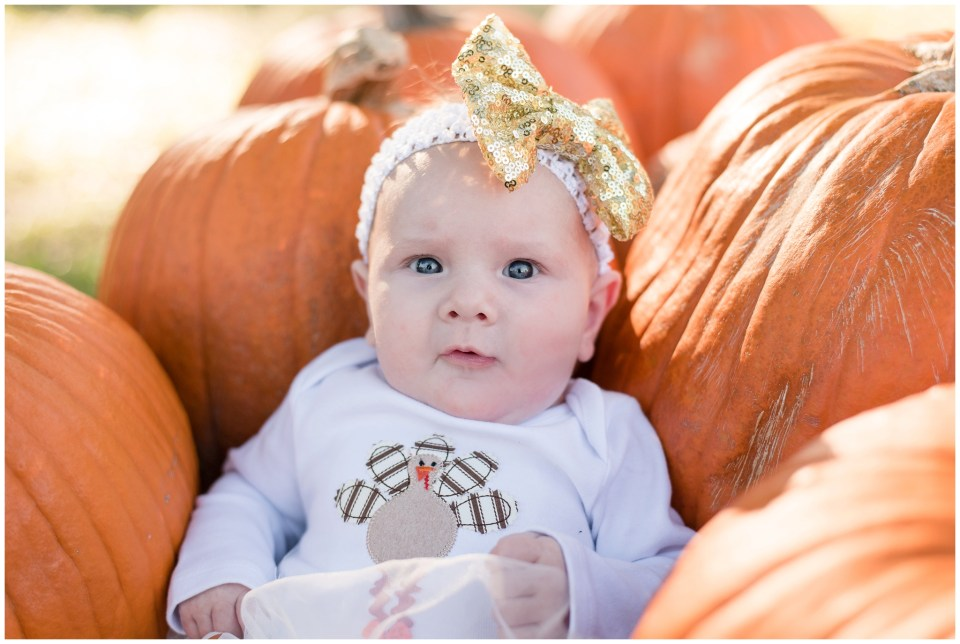 Kingwood child photographer images of Little One client's 3 month portrait session in a pumpkin patch