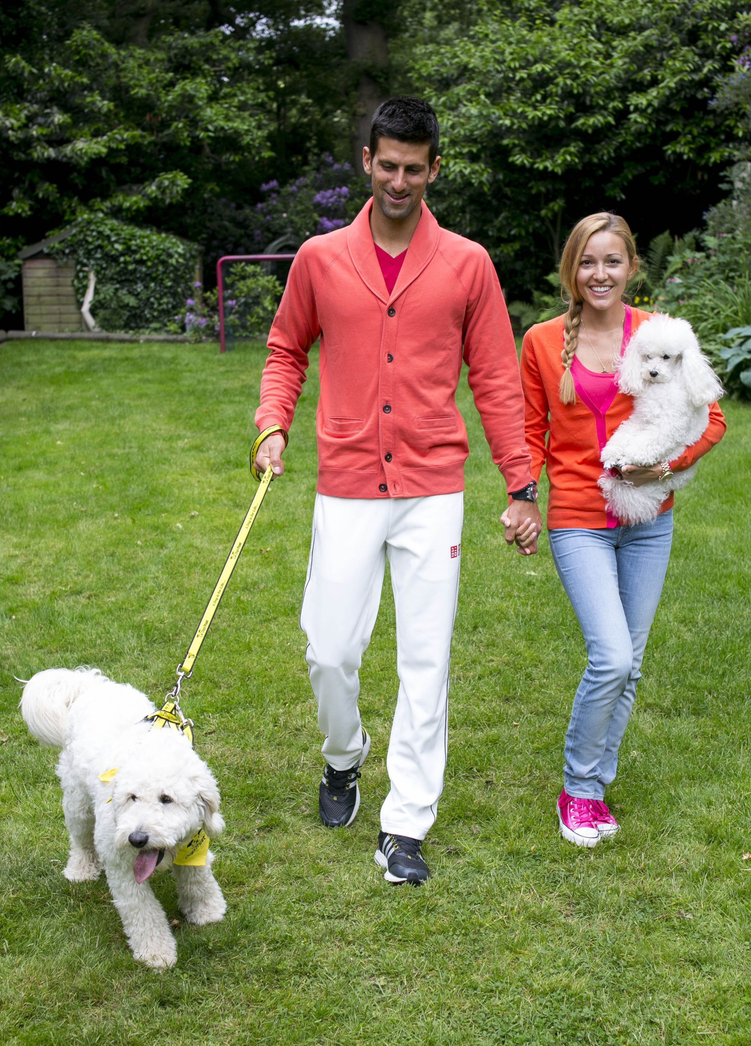 Djokovic names dog for Dogs Trust. EDITORIAL USE ONLY: World number one tennis player and dog lover Novak Djokovic with his girlfriend Jelena Ristic and their pet poodle, Pierre, play with Goldendoodle Bella, a Dogs Trust rescue dog, which Novak named this morning at his temporary residence in Wimbledon, south west London, to raise awareness of Dogs Trust and help find Bella a new home. PRESS ASSOCIATION Issue date: Friday June 21, 2013. Photo credit should read: John Phillips/PA Wire URN:16865807