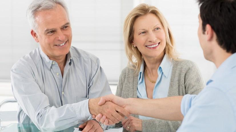 Senior Happy Couple Shaking Hand With Financial Advisor