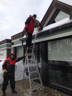 The crew clears icicles from the roof.