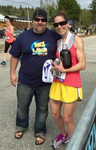 Half Marathon Winner Abeby Nyland poses with the race director, while showing off  her prize, a gallon of authentic New Hampshire maple syrup, and