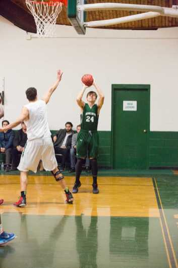Adam Mikula '17 takes a jump shot. Photo by David Barron.