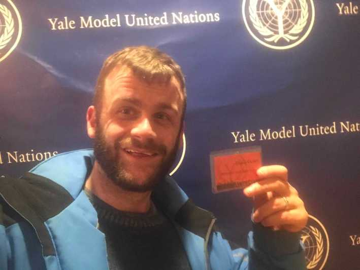 Chaperone David Cutler '02 poses in front of the Yale Model United Nations backdrop. Photo by Generous Passerby
