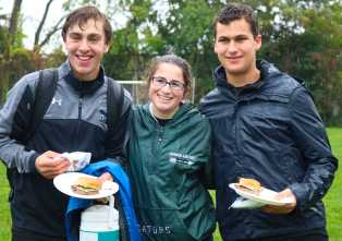 Olivier Khorasani '20, Catherine Leader '20, and Miles Munkacy '20 enjoy food before the girls play. Photo by Michelle Levinger '19.